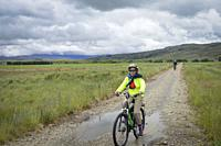 Woman bicycling on the Central Otago Rail Trail, South Island, New Zealand.