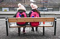 Stockholm, Sweden Two identical looking girls at a tram stop in Liljeholmen.