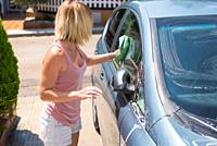 Young woman cleaning car with microfiber cloth. Car detailing.