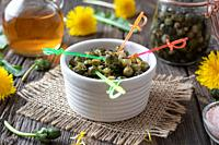 False capers made from young dandelion buds on a table.