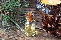 A bottle of essential oil with fresh pine branches.