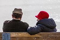 Older couple in conversation on a bench along the Steveston waterfront in British Columbia Canada