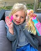 Little girl, 3 years old, holding a Barbie doll.