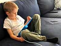 Boy, five years old, lying with a tablet computer in Scania, Sweden.