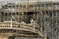PARIS, FRANCE - 19 APRIL 2019 Notre Dame cathedral, a man removes charred timber from the roof. The remains of the melted scaffolding behind him is wi...