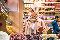 Beautiful Muslim woman in headscarf and fashionable modern clothes looks at spices sold on stall in Egypt Bazaar in Eminonu,Istanbul,Turkey. Modern Mu...