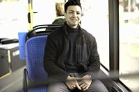 young pleased man sitting in bus, in Munich, Germany.