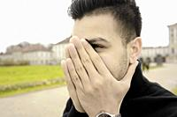 young man covering face with folded hands, in Munich, Germany.