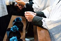priest with hands joined in prayer in church with rosary.