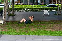 Singapore, Republic of Singapore, Asia - A man is doing sit-ups in the central business district at Marina Bay.