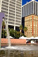 A purple fountain gushes in Pershing Square, surrounded by the skyscrapers of downtown Los Angeles.