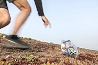 Male jogger picking up litter while running on trail in Spain. Plogging (picking up litter while jogging) is a Scandinavian lifestyle trend where jogg...