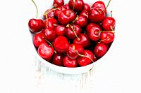 Cherries in a white bowl on a table