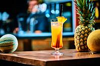 Cocktail with pinapple and melon in a bar on a blurry pub background. Copy space.