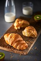 Croissant with milk on the wooden cutting board.