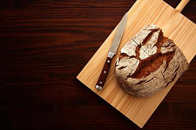 Rye bread and knife on board in dark wooden table top view.