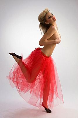 Beautiful woman in red diaphanous skirt dancing on grey background.