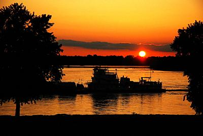 A River Barges Glides past the Setting Sun Alng the Mississippi River near Memphis, TN.