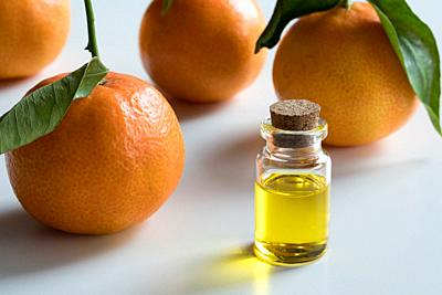 A transparent bottle of tangerine essential oil with fresh tangerines on white background.