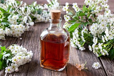 A bottle of herbal tincture with hawthorn flowers.