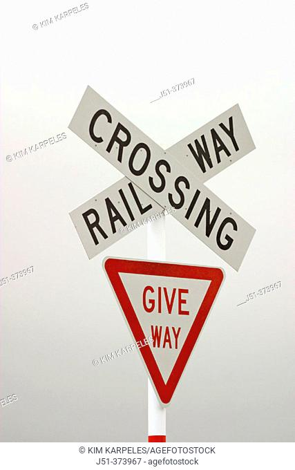 Railroad crossing sign, give way sign, foggy day. Fairlight. New Zealand