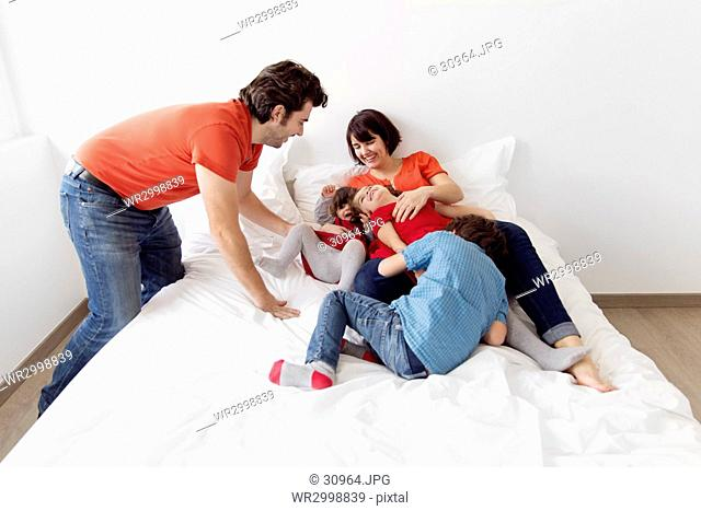 Man, woman and three children lying on a bed, playing and smiling