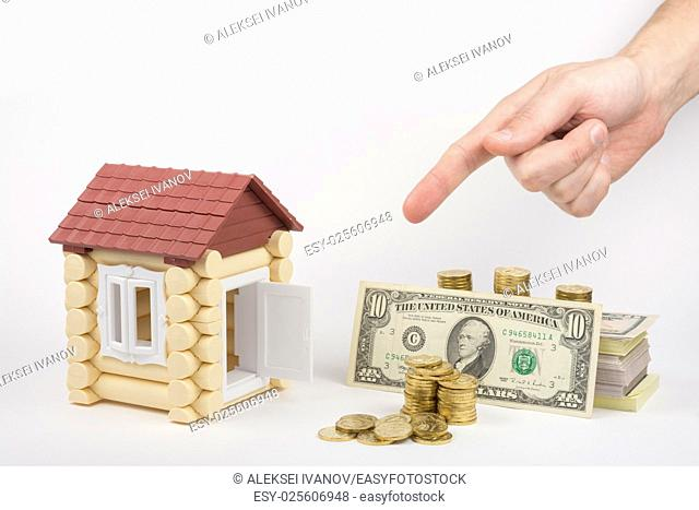 Toy house, lie near the money to buy, hand on top shows a finger