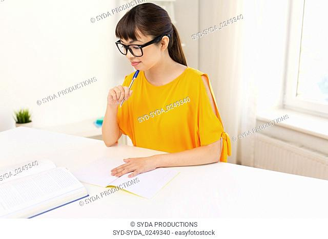 happy student girl with book and notebook at home