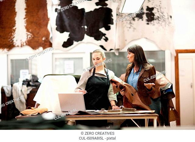 Worker and customer in leather workshop