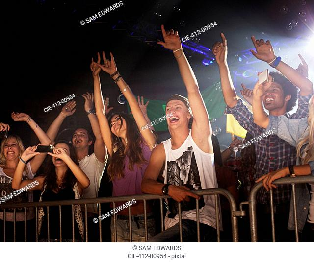 Enthusiastic crowd with arms raised behind railing at concert