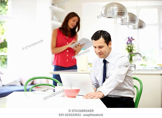 Couple Using Digital Devices At Breakfast Table