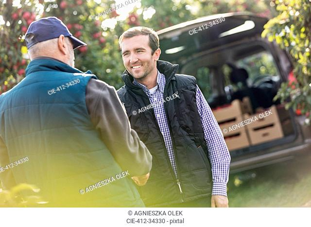 Smiling male farmer and customer handshaking in apple orchard