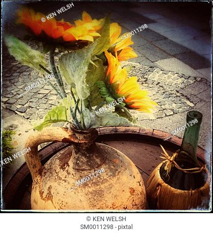 Sunflowers in old fashioned clay water jug beside chianti style bottle