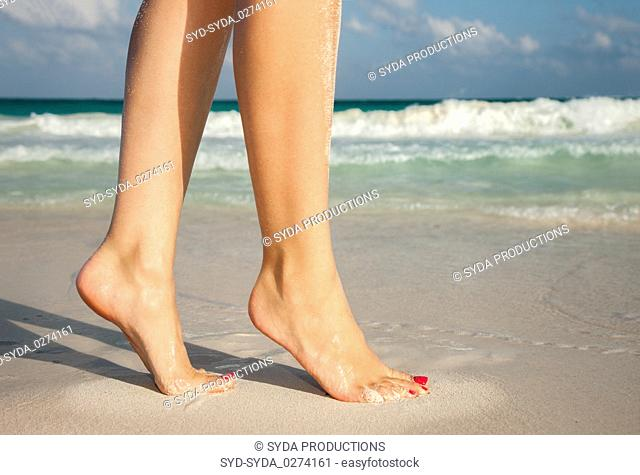 closeup of woman legs walking on beach sand