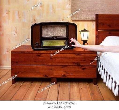 Woman`s hand turning radio on or off. Old classical retro radio and lamp on bedside tabel