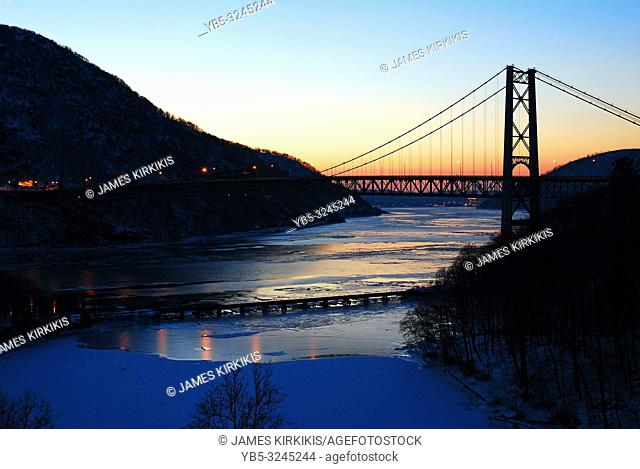 The sun rises over icy Hudson River and Bear Mountain Bridge