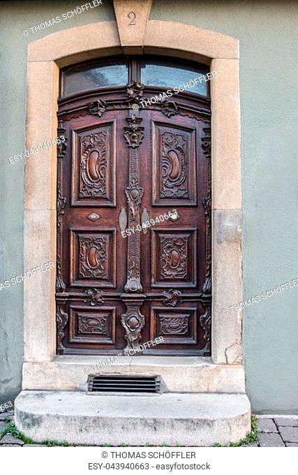 Old door of a historical building with stairway and house number