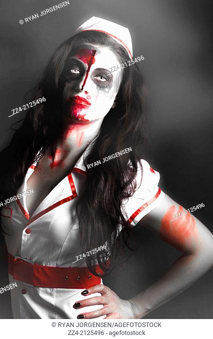 Foggy horror scene of a scary zombie nurse posing in the shadow of darkness with facial wounds and a bloody mouth
