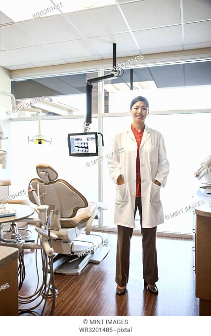 A portrait of an Asian female dentist in her office
