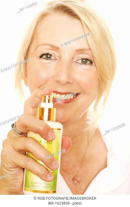 Woman, 49, spraying with a perfume bottle