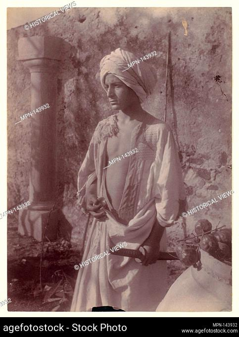 [Young Man in White Robe and Head Gear Holding Scabbard, Sicily, Italy]. Artist: Wilhelm von Gloeden (Italian, born Germany