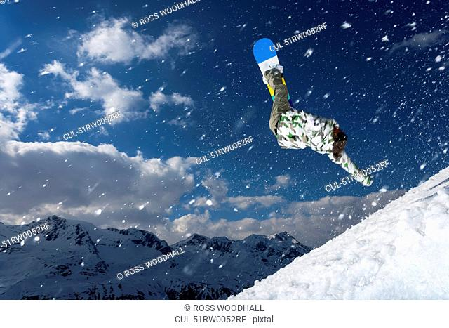 Snowboarder jumping on snowy slope