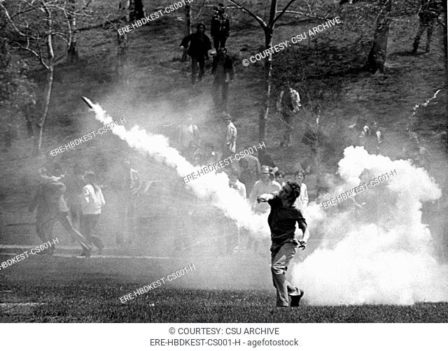 KENT STATE UNIVERSITY, student tosses a tear-gas bomb back at the National Guard who fired it to disperse the crowd