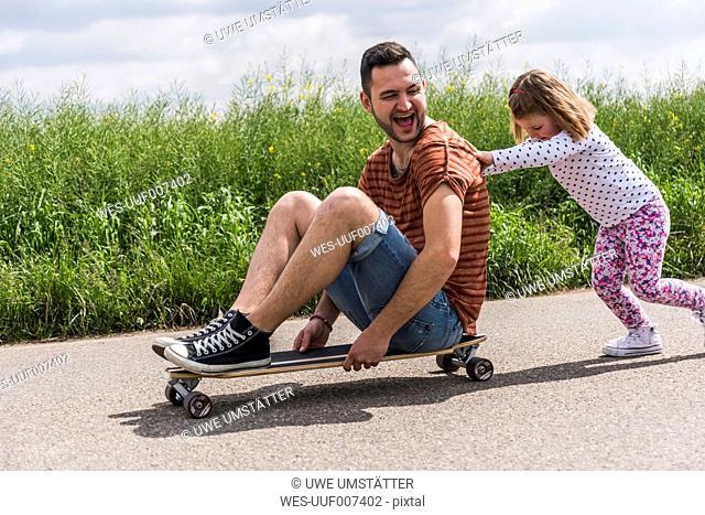 Daughter pushing father on skateboard
