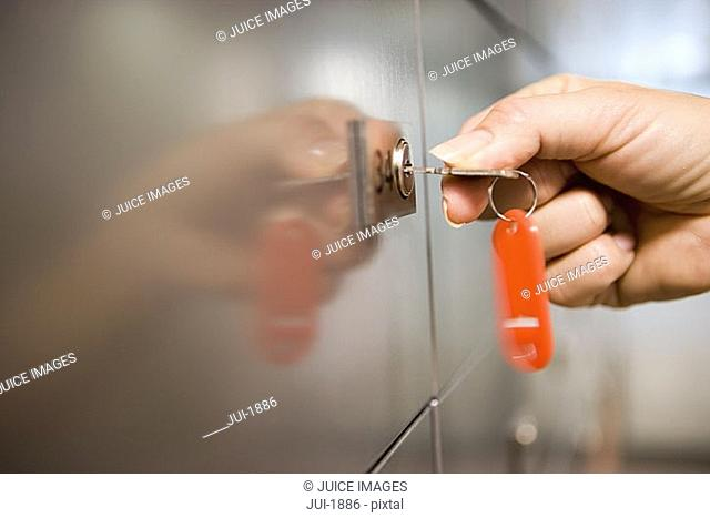 Woman holding red key ring, turning key in door lock, side view, close-up, focus on hand
