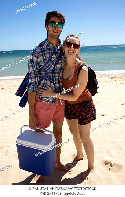 young couple on vacation at the beach, here free of crowds natural Salema beach in Costa Vicentina Natural Park, Vila do Bispo, Algarve, Portugal, Europe