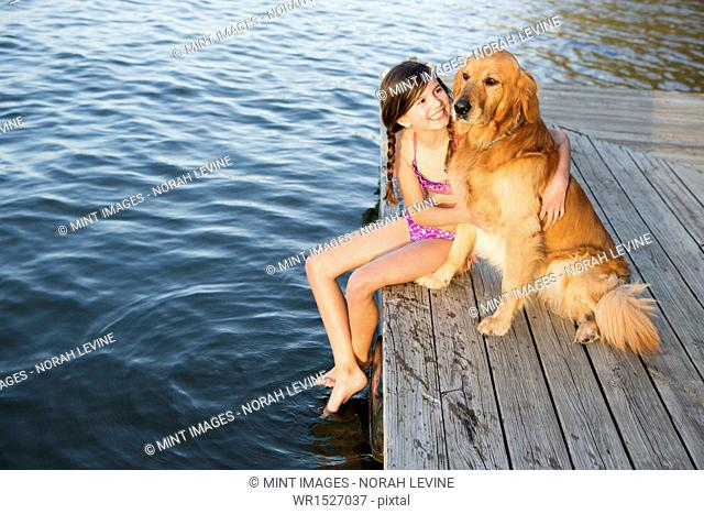 A girl and her golden retriever dog seated on a jetty by a lake