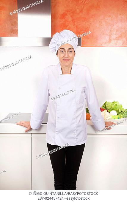 portrait of brunette chef woman with professional jacket and hat black trousers in white and orange kitchen