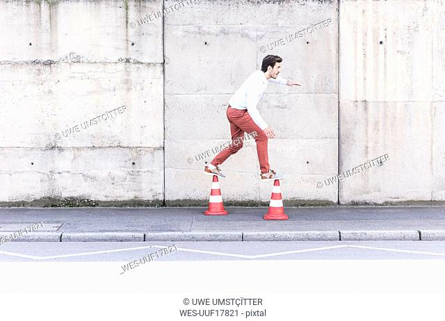 Young man balancing on traffic cones in front of concrete wall