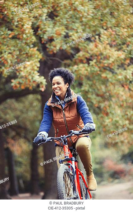 Smiling woman bike riding in autumn park